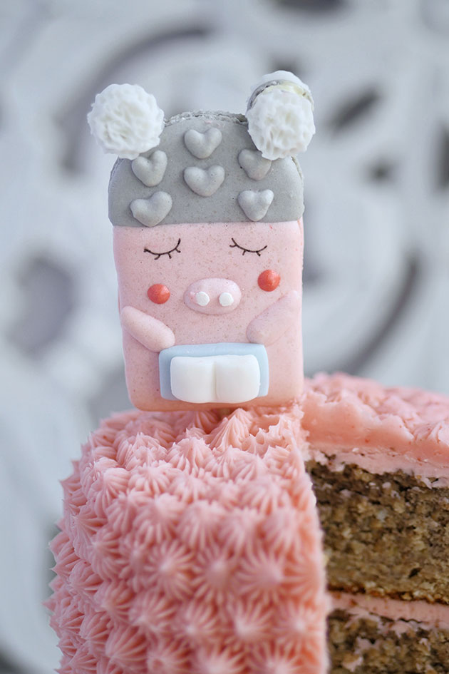 Small pink piggy macaron on a cake.