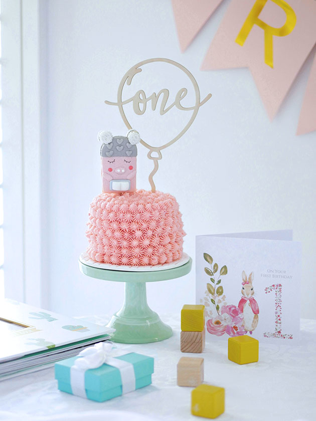 Small pink smash cake on a table with birthday decorations.
