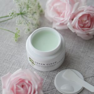 A tub of clean make up remover in seafoam green color shown with roses.