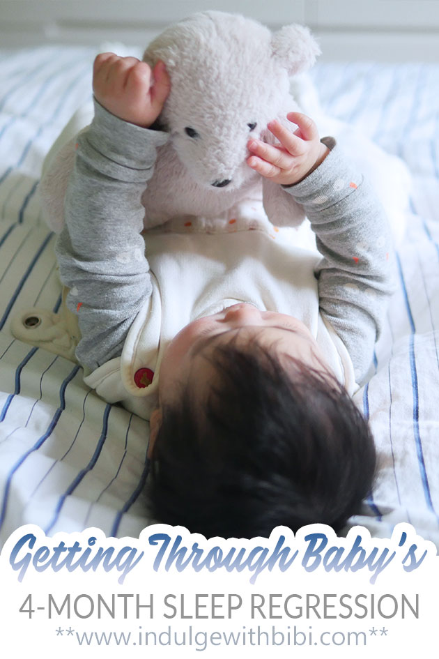 4-month old baby holding onto a teddy bear on the bed.