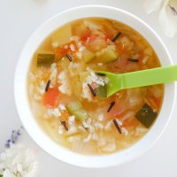 Close up of wild rice veggie soup with baby spoon inside.