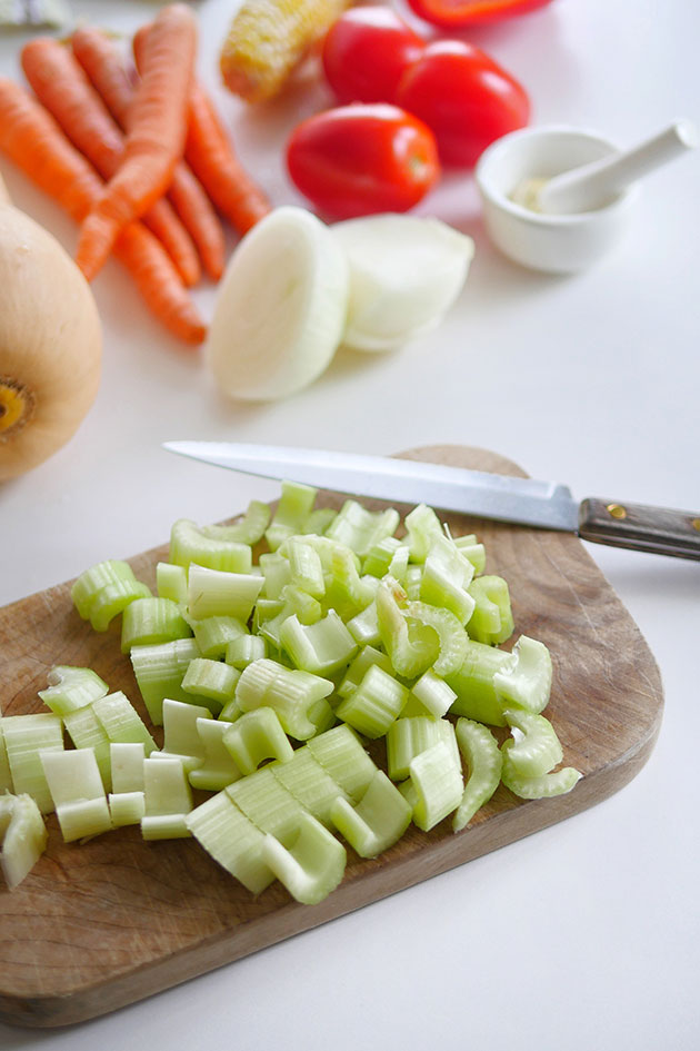 Diced celery on cutting board with knife.