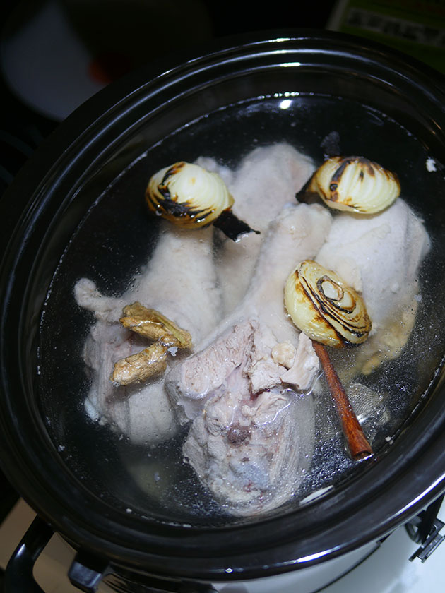 Turkey drumsticks inside the crockpot with the onion and spices.