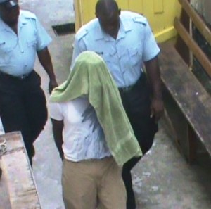 The Cop hides his face during his initial court appearance in April 25.