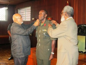 Colonel Lovell being badged by President Ramotar and Dr. Roger Luncheon. [iNews' Photo]
