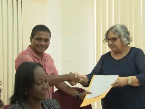 Executive Director and Company Secretary of Telcor, Randy Depoo receives the broadcasting license from Shadick.