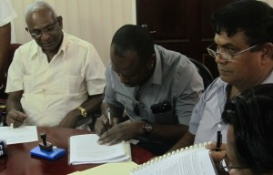 Minister Persaud and Robert Johnson sign the contract. [iNews' Photo]