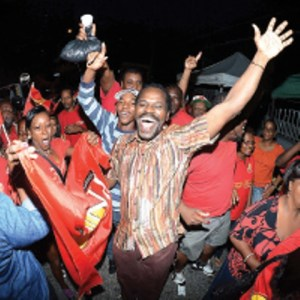 People's National Movement (PNM) Senator Fitzgerald Hinds celebrates with party supporters last night on his arrival at Balisier House in Port of Spain. [Trinidad Express Photo]