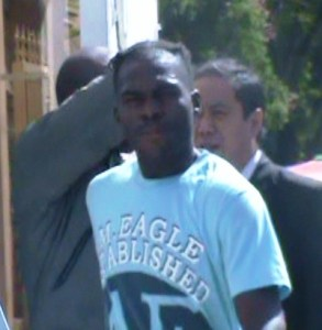 Dwayne Anthony exits the Magistrate's Court (in blue shirt) while Richard Bourne hides his face. [iNews' Photo]