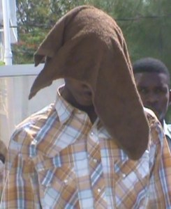 Jameen Farheem hides his face as he leaves the Georgetown Magistrate's Court. [iNews' Photo]