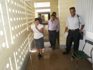 Minister Baksh inspects the flooded bottom flat of the Secondary School .