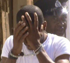 Jermaine Fenty hides his face as he exits the Georgetown Magistrate's Court. [iNews' Photo]