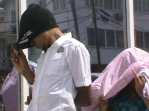 Alair Hendricks and Alicia Gilkes hide their faces as they exit the Magistrate's Court. [iNews' Photo]