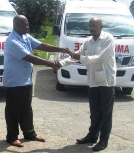 Junior Local Government Minister, Norman Whittaker receives the keys to the ambulances. [iNews' Photo]