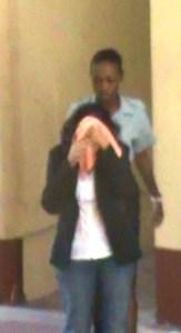 Sadika Leona Odie hides her face. [iNews' Photo]