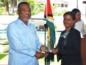 Prime Minister Samuel Hinds presents the daughter of Opposition Member of Parliament Deborah Backer, her  award for 14 years of service.