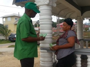 APNU Member, Joseph Harmon interacting with a resident of Bartica.