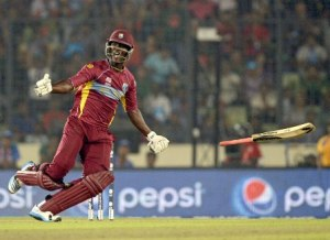 Darren Sammy celebrates the win by tossing his bat in the air