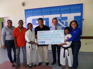Mr. Shaun McGrath, Mr. Frank Woon-A-Tai  and members of the Guyana Karate College accept the cheque from GT&T's PRO Nadia De Abreu and Marketing Officer Abena Fung
