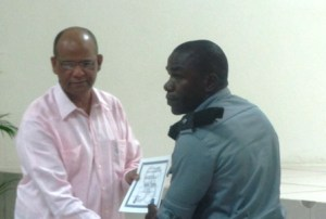 Home Affairs Minister, Clement Rohee hands over a certificate to one of the SWAT members. [iNews' Photo]