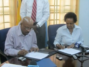 Local Government Minister Norman Whittaker and United Nations Development Programme (UNDP) Resident Coordinator Khadija Musa sign the agreement. [iNews' Photo]