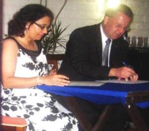 Ambassador Robert Kopecky and Melinda Janki sign the agreement.