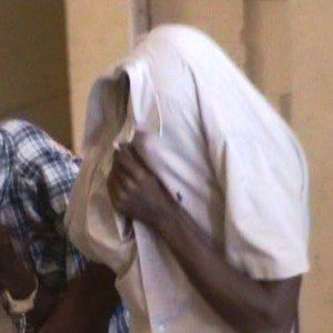 Paul Branson hides his face during his appearance at the Georgetown Magistrate's Court. [iNews' Photo]