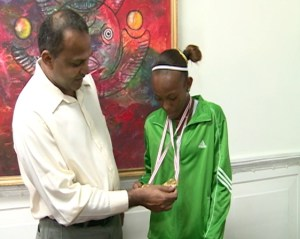 Sport Minister, Dr Frank Anthony inspects Cassy George's Gold Medals.