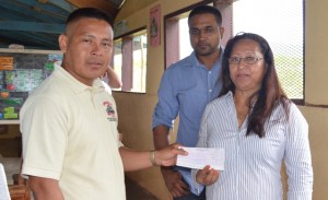 Minister of Amerindian Affairs Pauline Sukhai hands over a cheque worth $1.5M to Senior Councillor of Wowetta, Bertie Xavier