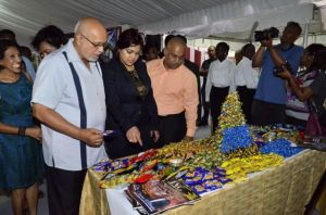 President Donald Ramotar gets an explanation about one of the products from Joint CEO of Sueria Manufacturing Inc., Teshawna Lall while Kaieteur News Publisher Glen Lall looks on.