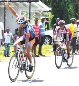 : Winner of stage three Guyana's Paul DeNobrega raises his hand to supporters as he nears the finish line; coming behind him is Darren Matthews