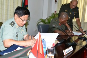 Major General, Kong Li from the People's Liberation Army of China and Chief of Staff, Guyana Defence Force, Brigadier, Mark Phillips signing the aid agreement at the opening ceremony of the Guyana-China Bilateral Conference.  [GINA Photo]