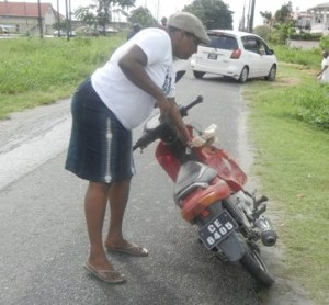 The dead man's wife picks up his motorcycle from the scene of the accident. [iNews' Photo]