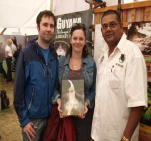 Two visitors to the Guyana  booth with GTA Director Indranauth Haralsingh. [GINA Photo]