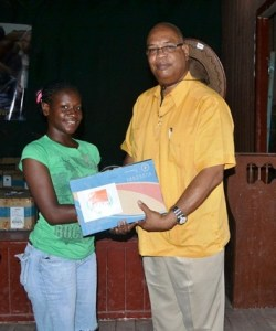Minister in the Ministry of Finance, Juan Edghill presents a laptop to one of the recipients. [GINA Photo]