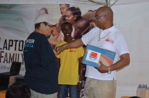 A resident of Linden receiving his laptop from Minister in the Ministry of Finance, Juan Edghill during the first day of the OLPF distribution exercise in that region. [GINA Photo]