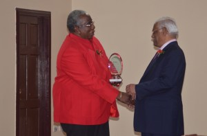 Chairman of the GMSA, Clinton Williams presenting an award to Chief Executive Officer of Gafoors, Sattaur Gafoor for the company's outstanding contribution to the building and construction industry. [GINA Photo]