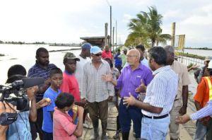 President Ramotar engaging residents of Cane Grove, Mahaica during a flood check on the East Coast Demerara. [GINA Photo]