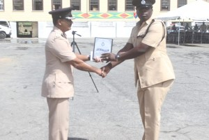 Runner up for Best Cop, Jermaine Dufu receives his incentive from Assistant Commissioner David Ramnarine. [Sonell Nelson]