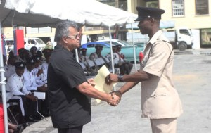 Best Cop Inspector Johnson receives his prize from Gerry Gouveia. [Sonell Nelson]