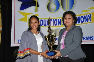 Minister Manickchand presents the best graduating student,  Duviena Badray, with a trophy.  Badray was also presented with two other awards.