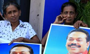 Mahinda Rajapaksa's supporters hold posters of their leader. The incumbent was standing for a third term in office against one of his closest allies, Maithripala Sirisena. Photograph: Buddhika Weerasinghe/Getty Images