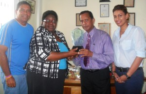 Grace Mc Calman (second left) hands over the plaque to Bish Panday in the presence of John Goede, ITF Development Officer for the Caribbean and Elizabeth Persaud, Treasurer of the Guyana Lawn Tennis Association. [iNews' Photo]