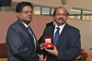 Finance Minister Dr. Ashni Singh receives a copy of the commemorative coin from Bank of Guyana Governor Dr. Gobind Ganga.