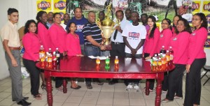 General Manager, Robert Selman hands over the winning trophy to Director of Petra, Troy Mendonca in the presence of Busta staff members. [iNews' Photo]