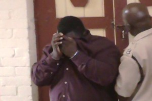 Richard Stanton hides his face as he exits the Georgetown Magistrate's Court. [iNews' Photo]