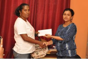 Mrs. Prasad receiving a donation from IAC Executive Member, Ms. Yvette Ramharack (Secretary)