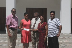 Ramsay Ali receives cheque from Gloria Narine in the presenece of her husband Noel, daughter Soraya and son Navin