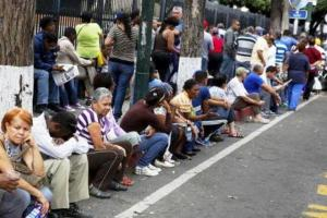 People queue outside a state-run Bicentenario supermarket as they wait to buy staple items