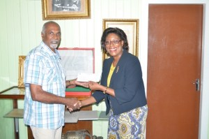 Tourism Minister Cathy Hughes presenting the sponsorship cheque to one of the organisers of the Rupununi Music and Arts Festival.